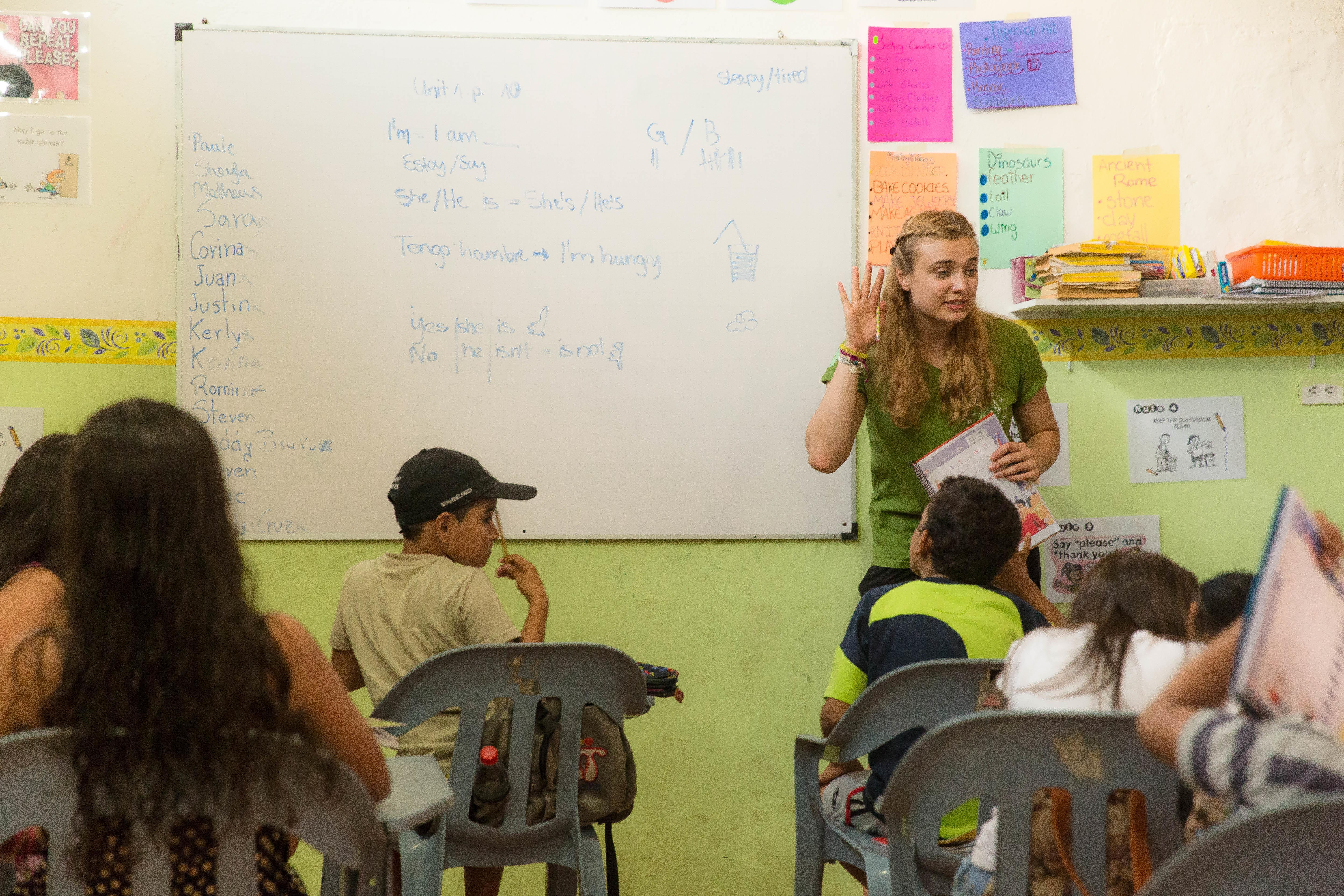 A volunteer teaching abroad works with students on a Projects Abroad placement.